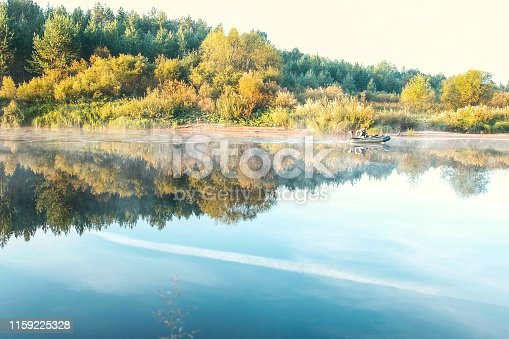 175421347 istock photo Fisherman on an inflatable motor boat floating on the river in the autumn. 1159225328
