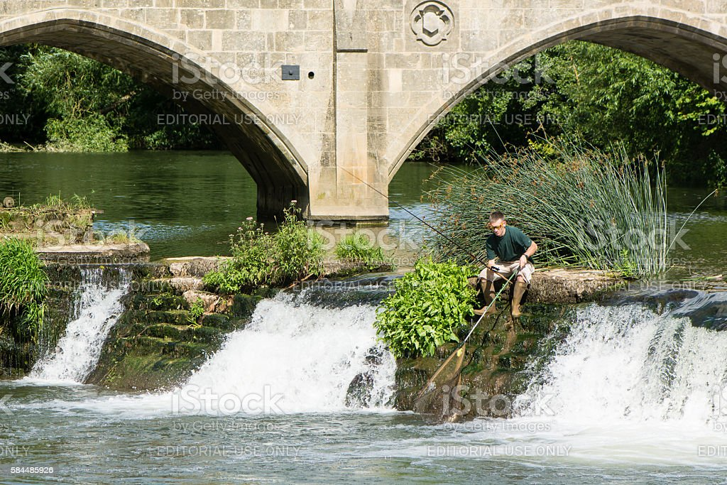 Fisherman on Bathampton Weir with rod and net stock photo