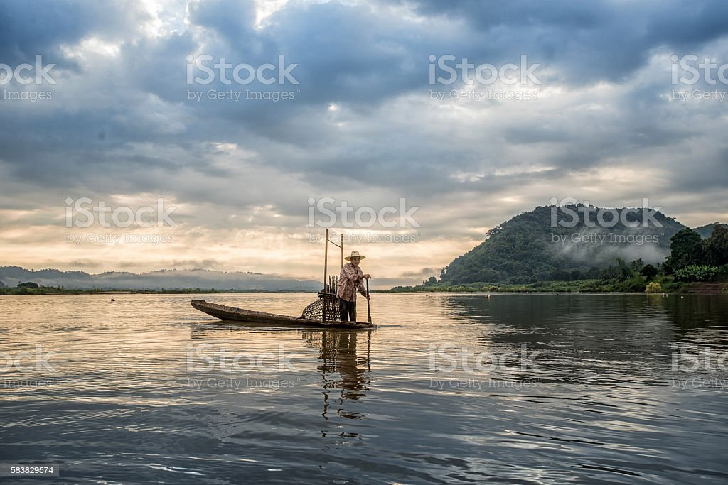 Fisherman on boat in action when fishing stock photo