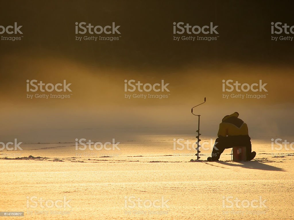 Fisherman on Frozen lake stock photo