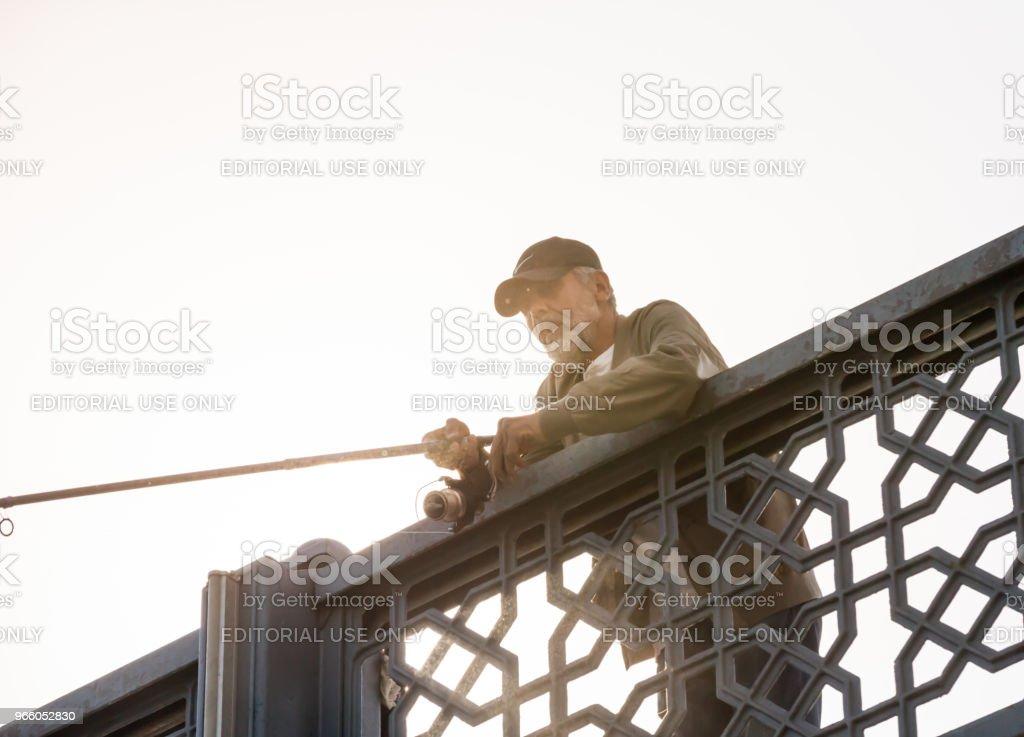 Fiskare på Galata bron över Bosporen i Istanbul - Royaltyfri Behornad Bildbanksbilder