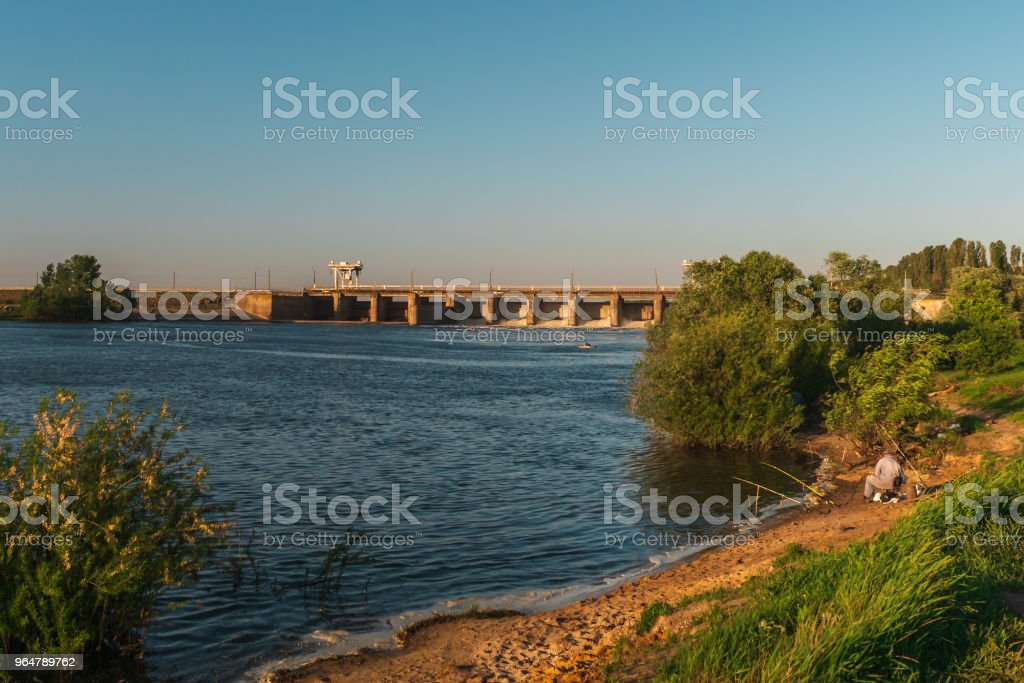 Fisherman on sand coast of river near industrial dum in sunset royalty-free stock photo