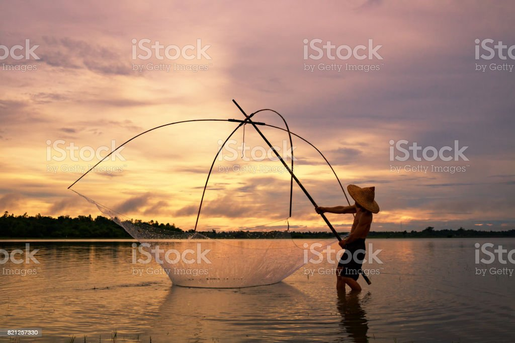 Fisherman on silhouette sunrise with gear fishing stock photo