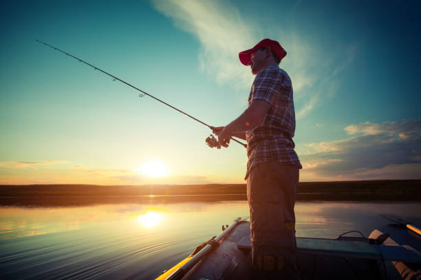Fisherman on the boat Man fishing in a pond from a boat at sunset freshwater fishing stock pictures, royalty-free photos & images