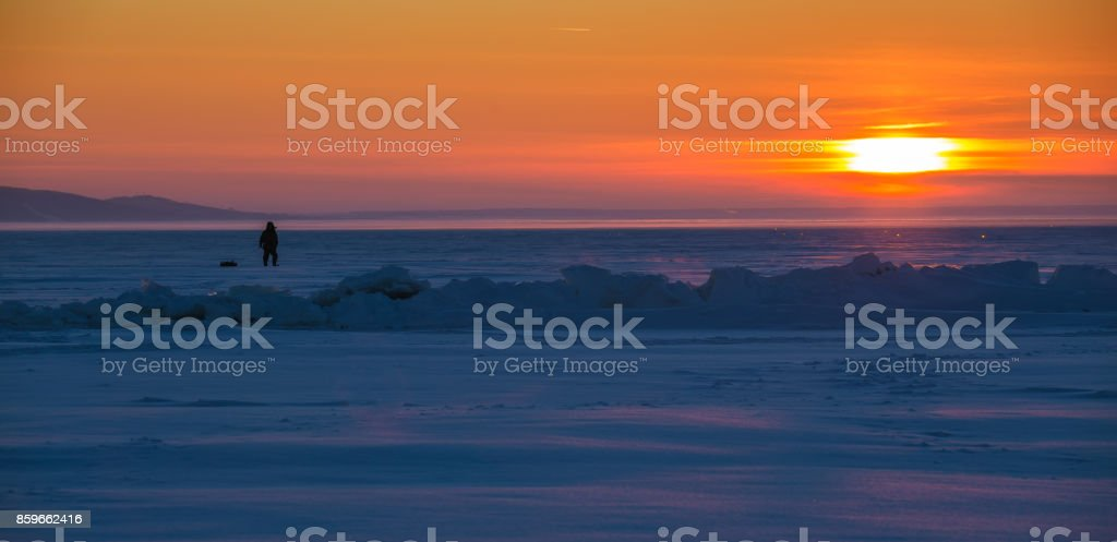 fisherman on the ice of the river at sunset stock photo