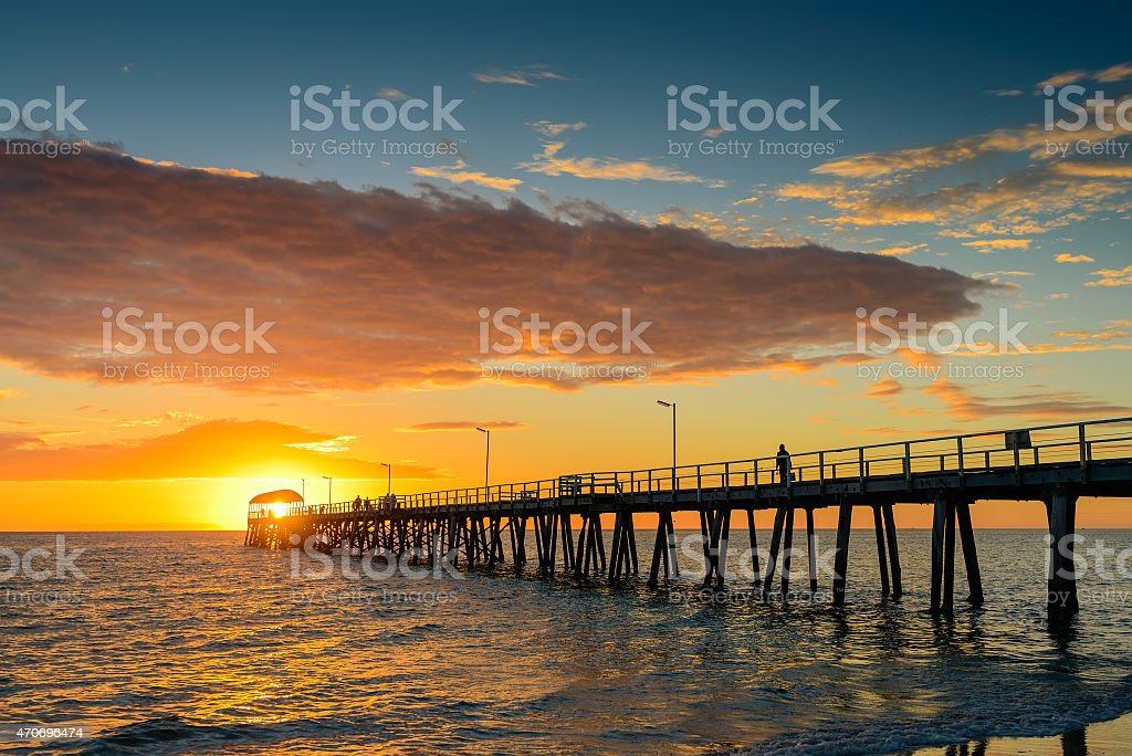 Fisherman on the jetty at sunset stock photo