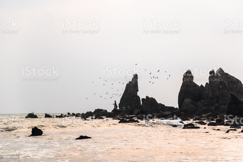 Fisherman on the rocky coast royalty-free stock photo