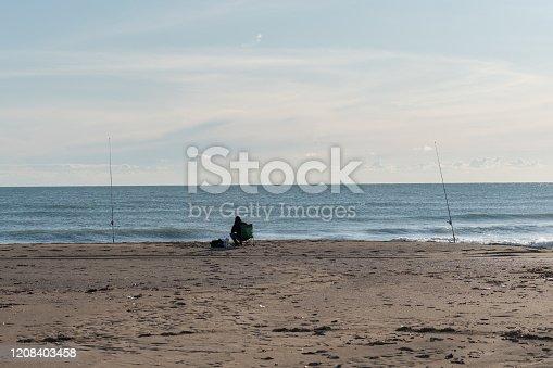 istock Fisherman on the sunny beach 1208403458