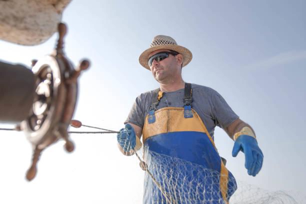 fischer auf der arbeit - segelhandschuhe stock-fotos und bilder