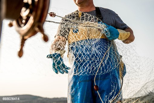 Part of fisherman's body, wearing yellow and blue pants and standing on a fishing boat while pulling the fishing nets in Koper, Slovenia. Boat wheel on the left side in blurred motion.