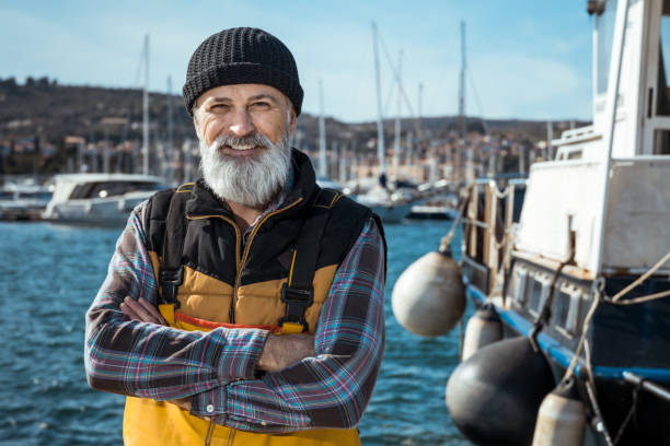 Fisherman Portrait of senior fisherman in front of sea fisherman stock pictures, royalty-free photos & images