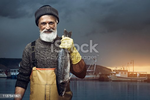 Portrait of senior fisherman holding big fish
