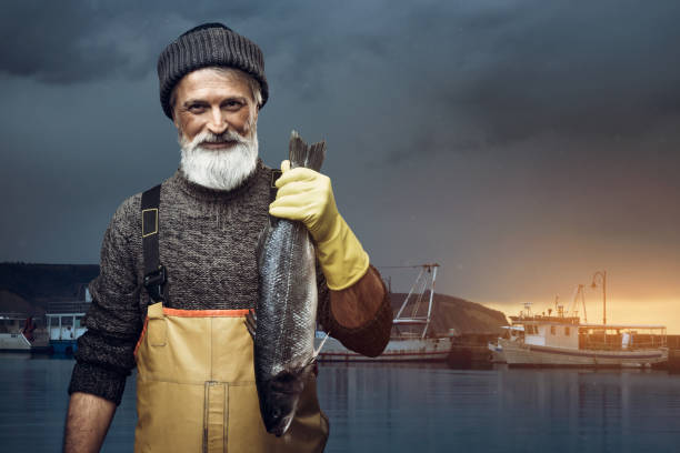 Fisherman Portrait of senior fisherman holding big fish fisherman stock pictures, royalty-free photos & images