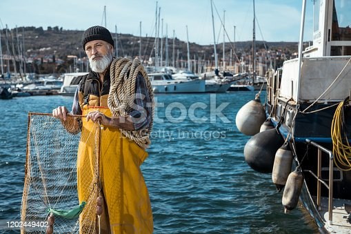 Portrait of senior fisherman in front of sea