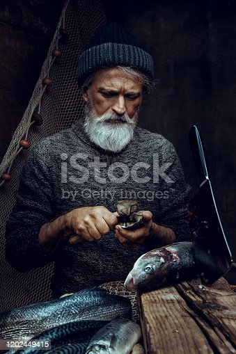 Portrait of senior fisherman cleaning fish