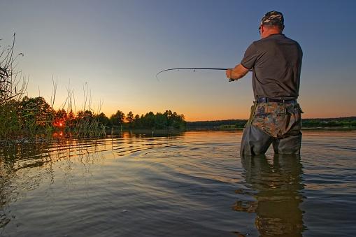 Fisherman catching the fish during sunset