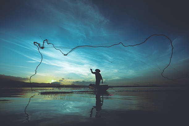 Fisherman Silhouette of fishermen using nets to catch fish at the lake in the morning fishing net stock pictures, royalty-free photos & images