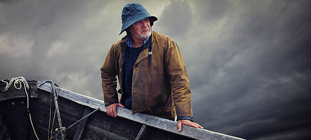 Fisherman Portrait, Stormy Sky and Dory, Nova Scotia Fisherman Portrait, Stormy Sky and Dory, Nova Scotia fisherman stock pictures, royalty-free photos & images