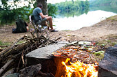 istock Fisherman preparing dinner on campfire, adventure lifestyle camping fishing concept 817409828