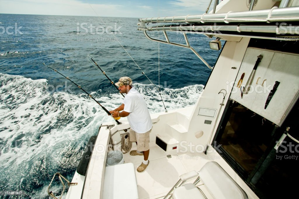 Fisherman Prepping Fishing Rods on Private Boat in Ocean stock photo