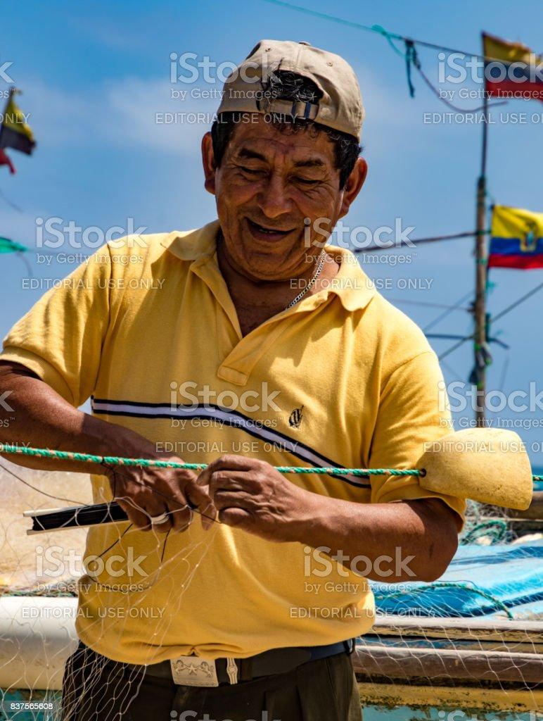 Fisherman repairs his net stock photo