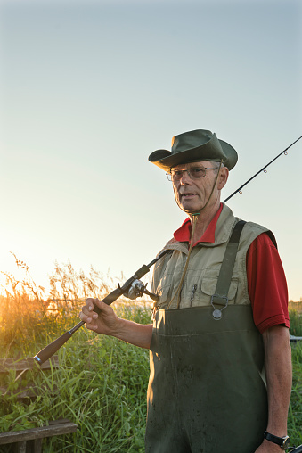 Portrait of a 65 year old  fisherman returning to his boat mooring after an evening of fishing. He wearing a pair of green waders and he is carrying a rod and net, he is surrounded by tall reeds that are growing at the waters edge where he keeps his boat. Photographed in the late evening light on Stege Nor on the island of Møn or Moen in Denmark.