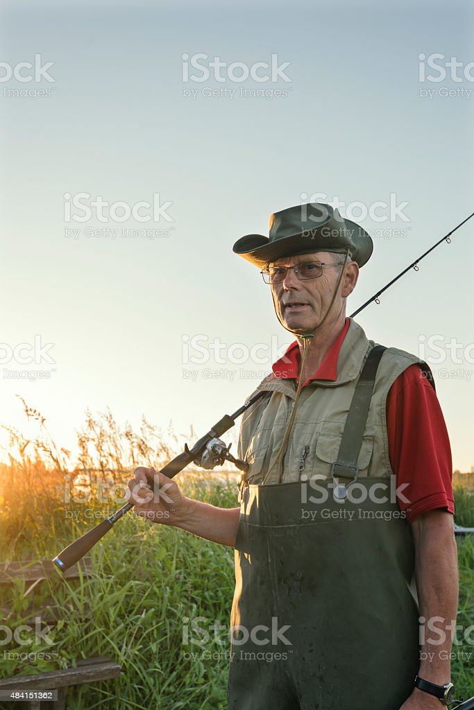 Fisherman Returning From Fishing Trip Surrounded By Reeds. stock photo