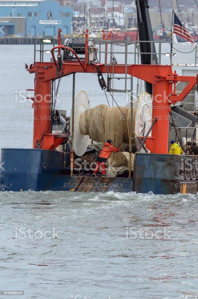 Fisherman securing net on trawler stock photo