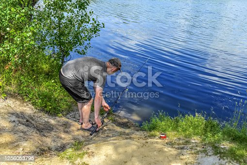istock Fisherman sets fishing rod on the shore of the lake - top view 1256053795