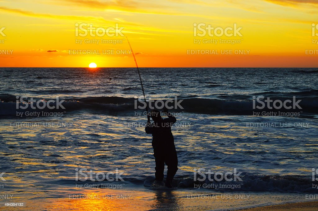 Fisherman silhouette at the seashore royalty-free stock photo