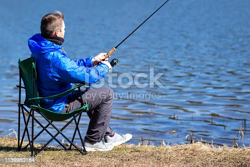 Fisherman sitting in chair with fishing rod catching fish on lakeside. Fishing