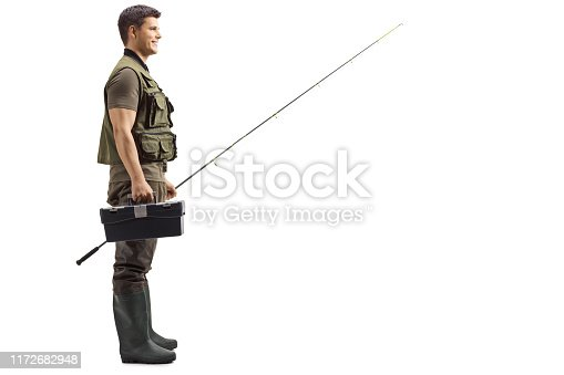 istock Fisherman smiling and standing with a rod and tool box 1172682948