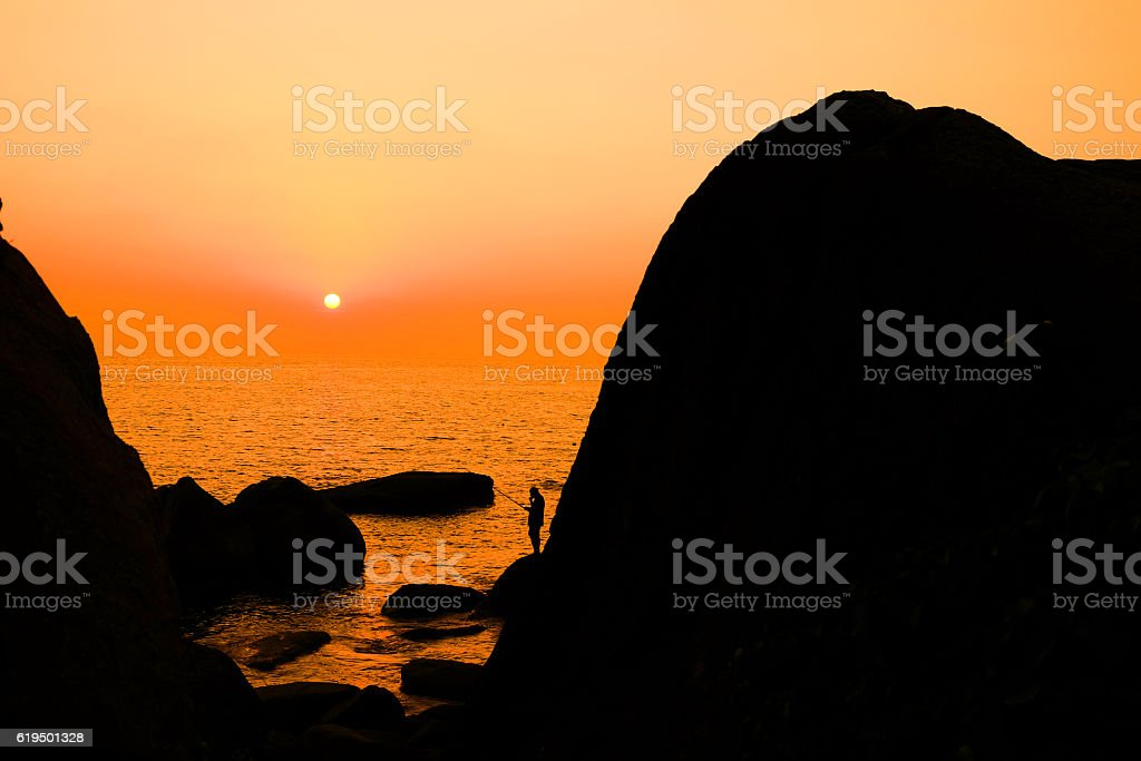 Fisherman standing between rocks on a beach in Goa, India stock photo
