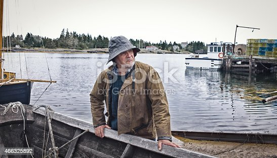 Fisherman pulling up a Dory on a slipway/wharf, Mahone Bay, Nova Scotia.  All gear and clothing is authentic to the era.  He has a southwester hat on and oilskin rain gear.  He is old with a white/grey beard.  Sea and sailboat make the background.  Leica camera photograph.