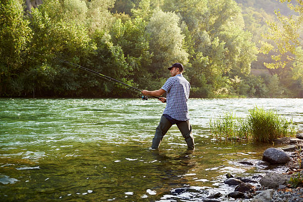 fisherman standing near river and holding fishing rod - fishing industry stock pictures, royalty-free photos & images