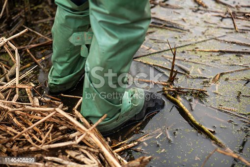 fisherman stands in the water in rubber waterproof boots for fishing.