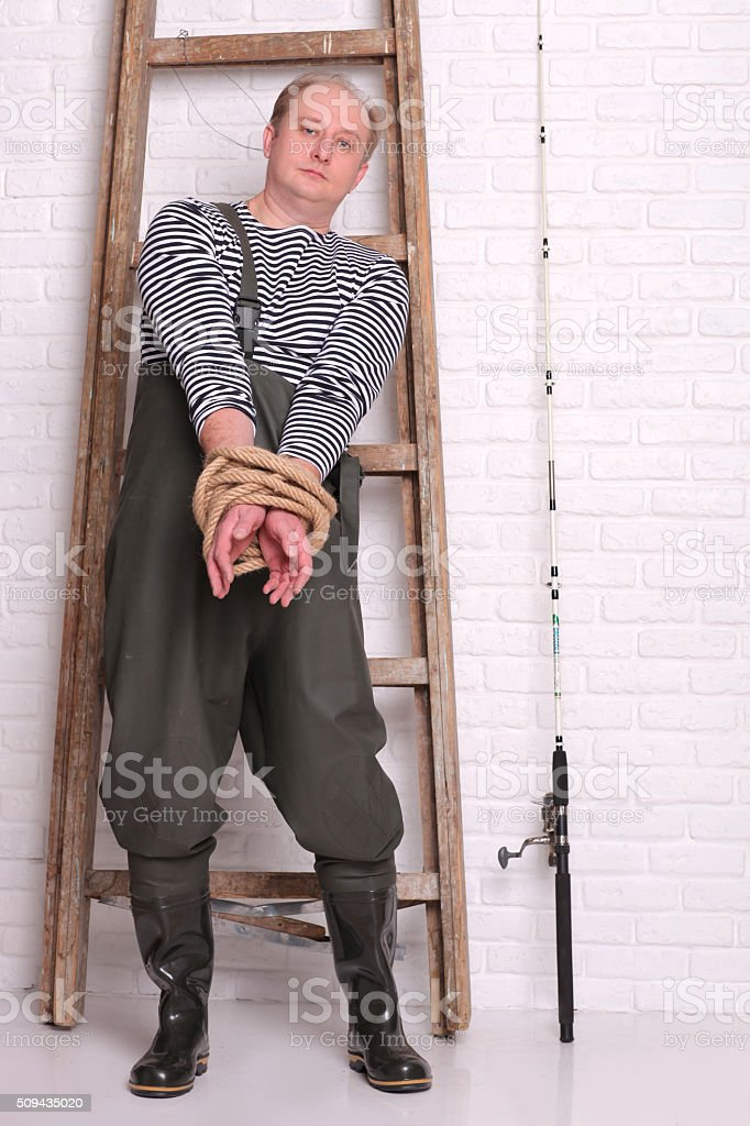 Fisherman stands near the ladder and hands tied rope stock photo