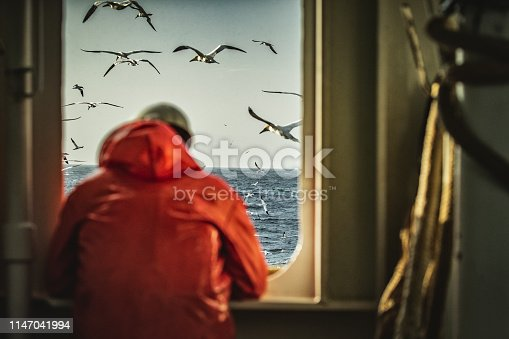 Fisherman staring at sea on the fishing boat deck