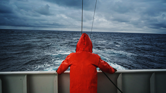 Fisherman staring at sea on the fishing boat deck, with a orange raincoat