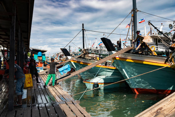 Fisherman throws back empty basket to fishing trawler stock photo