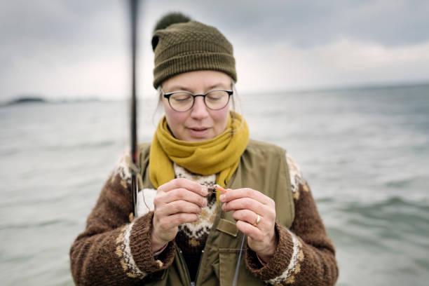 binden einer fliege auf ihre linie fischer - angeln dänemark stock-fotos und bilder