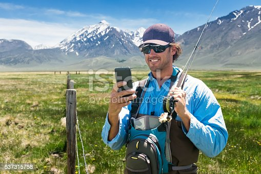 992209122istockphoto Fisherman Using His Phone In A Beautiful Mountain Meadow 537315758