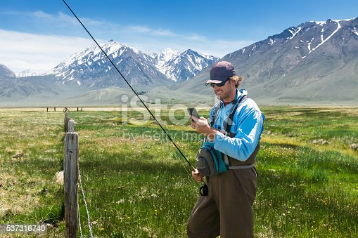 992209122istockphoto Fisherman Using His Phone In A Beautiful Mountain Meadow 537316740