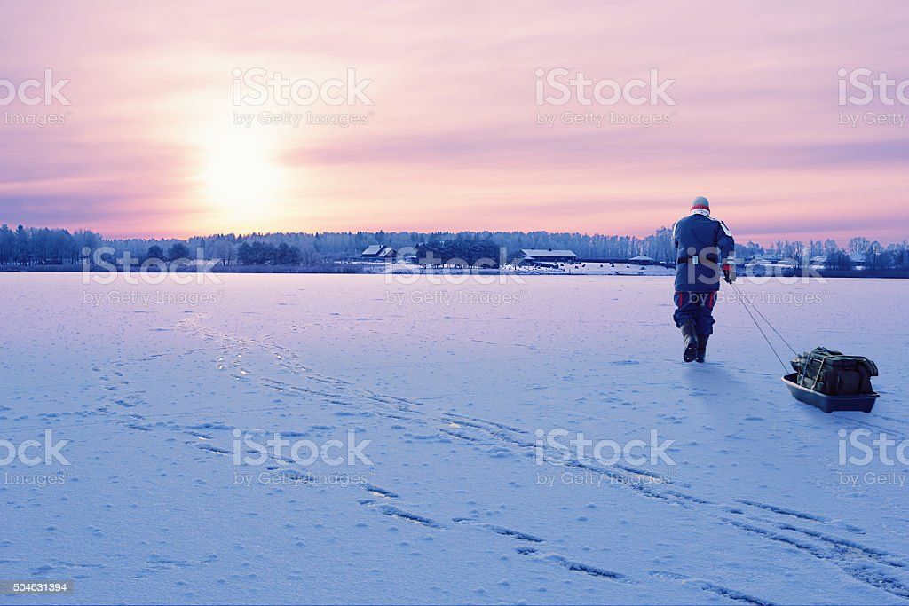 Fisherman walking on the frozen lake stock photo