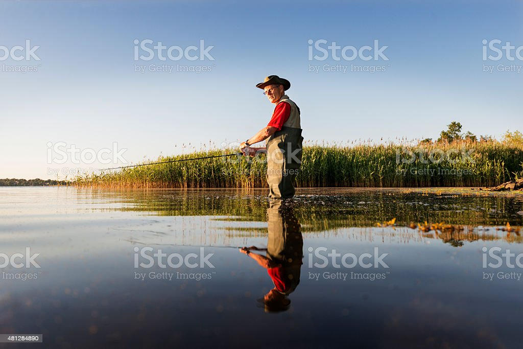 Fisherman Wearing Waders Waiting Patiently For a Bite. stock photo