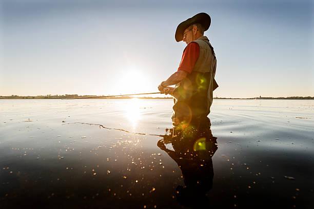 fischer mit schwimmer wartet geduldig auf einen snack. - angeln dänemark stock-fotos und bilder