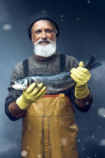 嵐の背景に大きな魚を持つ漁師 - 漁師 ストックフォトと画像