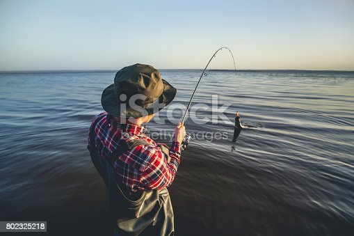 914030378 istock photo A fisherman with a fishing rod in his hand and a fish caught stands 802325218