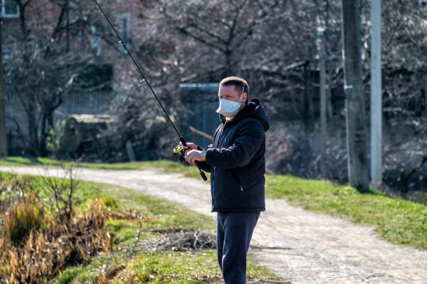 Fisherman with a spinning rod in his hands during an epidemic COVID-19 does not forget about quarantine rules stock photo