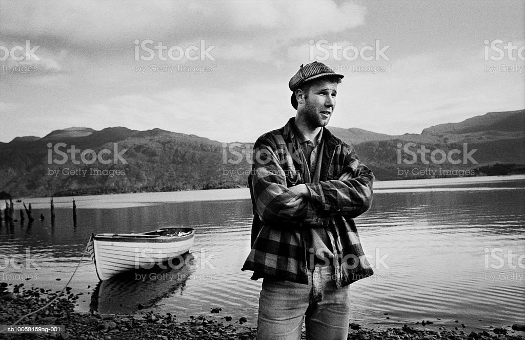 Fisherman with arms crossed at lake shore (B&W) royalty-free stock photo